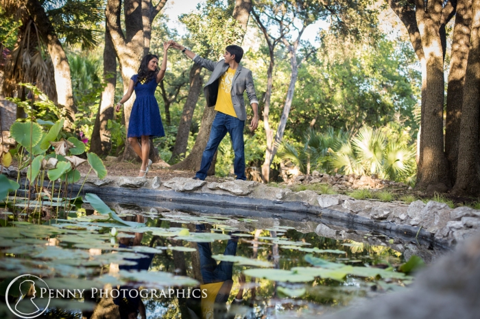 couple dancing by a pond in a garden during engagement portraits