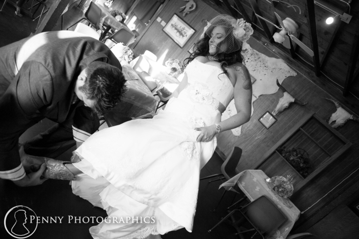Husband helps put brides shoes on