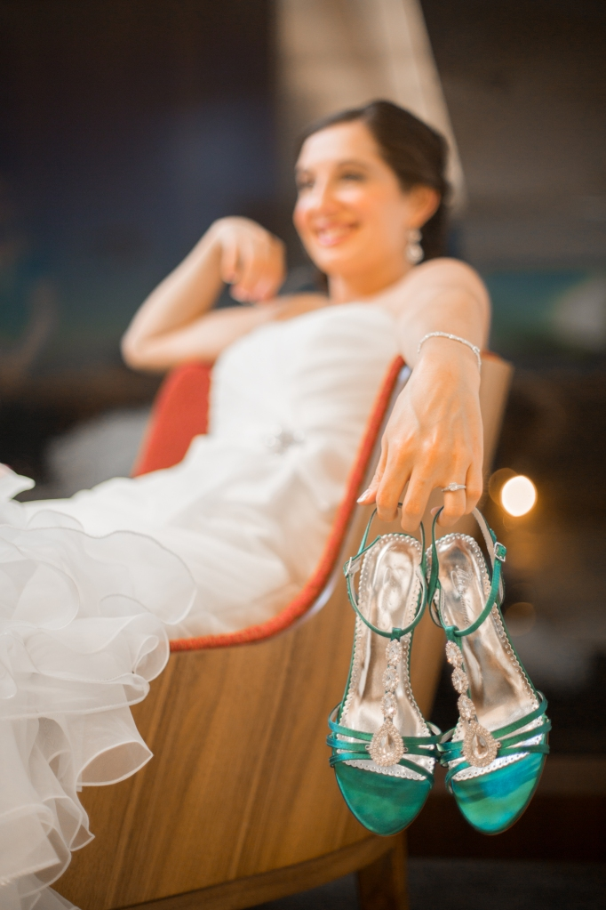 bride holding her blue shoes