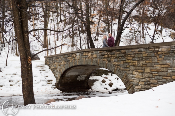 photos on the bridge during winter engagement session minnehaha falls