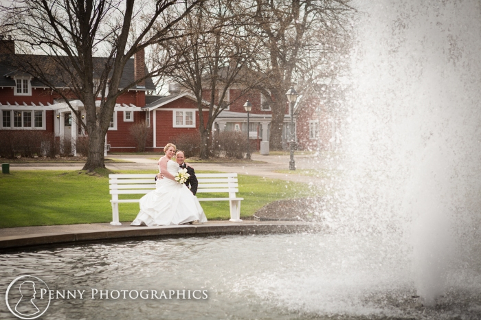 bride and groom sitting on bench by fountain at the Earle Brown Event Center MN