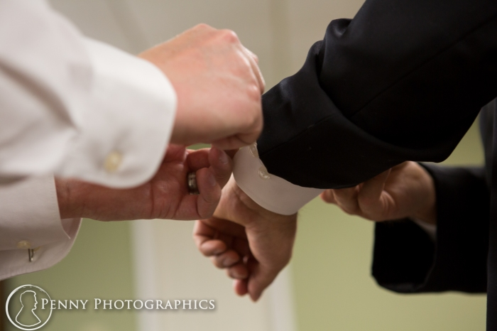 brother helps groom with cufflinks