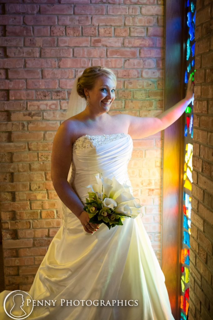 Bridal portraits by stained glass window inside church in Minnesota