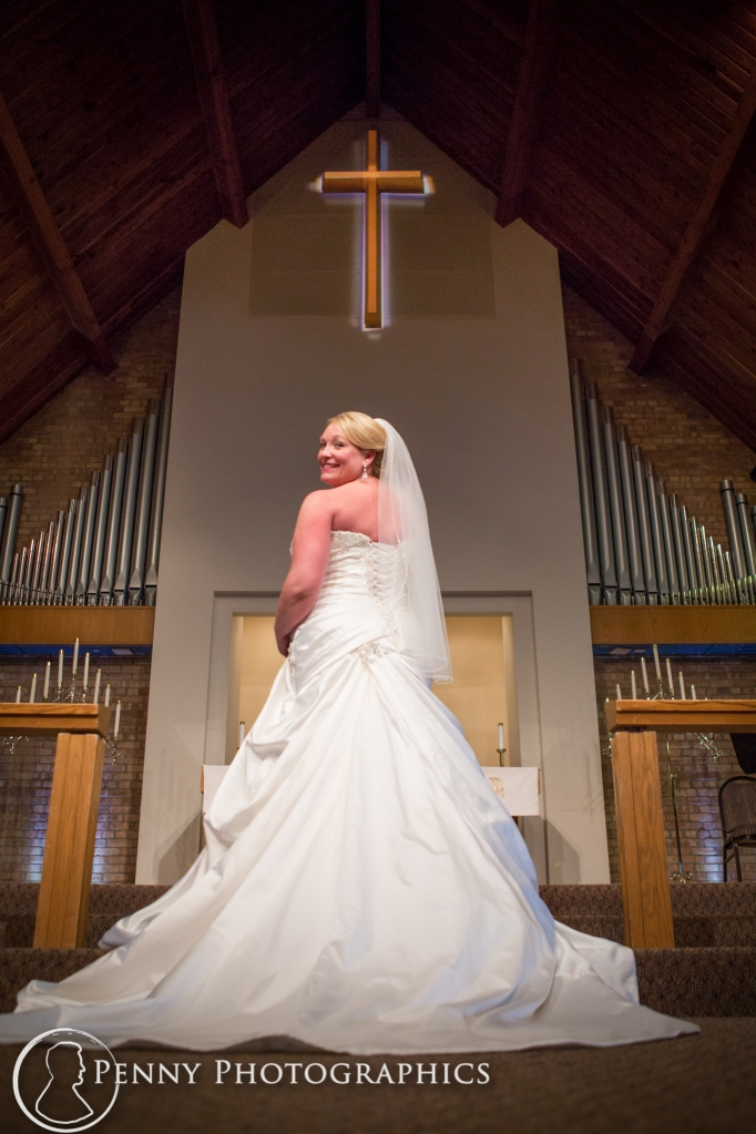 Bride standing at alter during portraits inside church MN