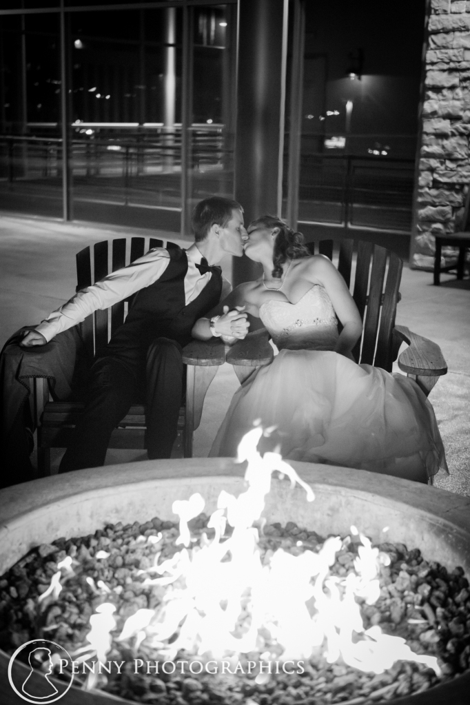bride and groom kissing by the fire pit outside Pinstripes Minneapolis