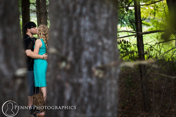 couple kissing inbetween trees