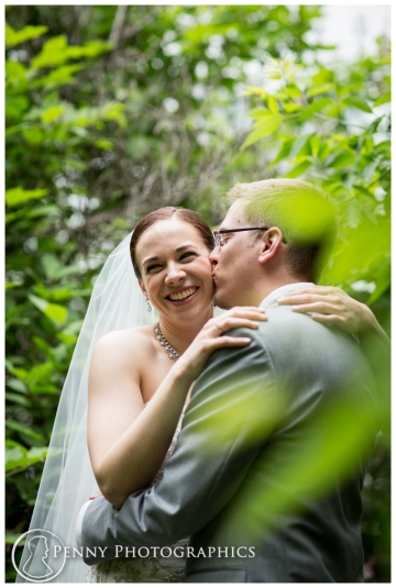 Bride and groom kissing in the trees